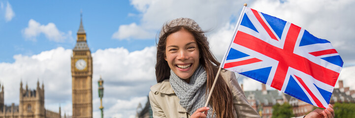 London travel tourist woman with Great Britain flag banner showing Union Jack Icon. UK European holiday destination Asian chinese girl holding United Kingdom British flag. Panorama crop.