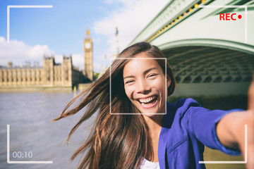 Wall Mural - Selfie portrait travel woman recording video vlog on mobile phone. Camera screen of Asian tourist girl on London Europe vacation vlogging talking on live stream. UK european tourism destination