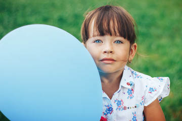 little girl with blue eyes and blue baloon looking at camera