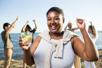 Dancing girl with drink enjoying beach party with her friends