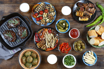 Dinner table with meat grill, bbq vegetables, salads, sauces, snacks and beer, top view