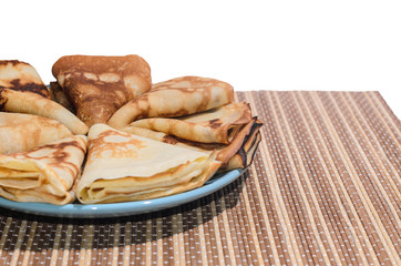 Russian traditional dishes - pancakes on a plate on a bamboo napkin