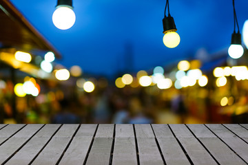 Image of wooden table in front of decorative outdoor string lights hanging on electricity post in night market with blur people. Christmas, festival and holiday concepts