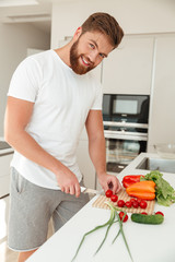 Vertical image of smiling bearded man with vegetable