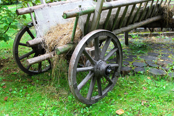 Old wooden cart with straw bedding instead of the seat.