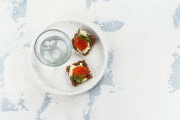 Vodka shots with ice and small snack sandwiches with red caviar on white background. Space for text