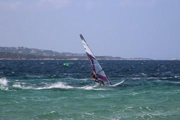 Windsurfing girl planing over the blue choppy sea (Porto Pollo, Sardinia, Italy)