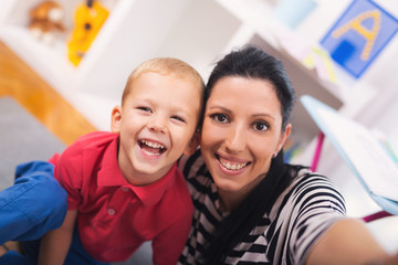 Mother with child photoshooting on smartphone selfie in the home room