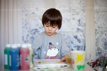 Cute little preschool boy, drawing picture at home