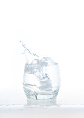 cool water, Ice cubes splashing into glass of water, water splashing from ice cubes being dropped in a glass.