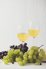 Two glasses of white wine, fresh grapes and pears