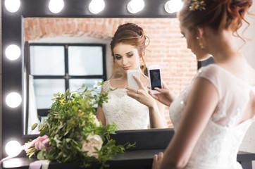 Young pretty bride making selfie near mirror