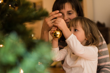 Mother helping daughter to decorate xmas tree