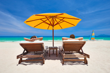 Family couple on tropical beach on deck chairs under orange umbrella