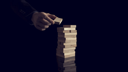 Male hand creating or building a tower of many wooden blocks over black background