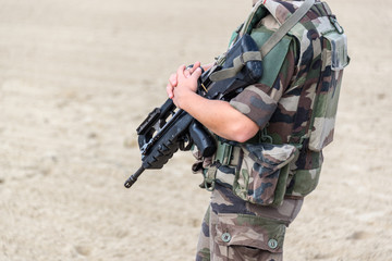 Close up of a French soldier with an automatic rifle, war and emergency state concept