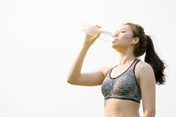 Asian woman holding water bottle in hand and drinking water and ready for running and exercise for health