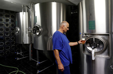 Brewer drafts a glass of beer in a micro-brewery owned by Litomerice bishopric in Litomerice
