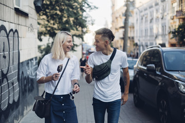 Attractive trendy hipster millennial couple or two friends walk on street in urban city, they laugh and giggle, make jokes and enjoy youth and life