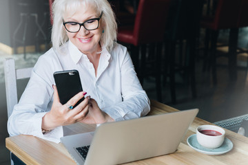 Smiling businesswoman dressed in white shirt is sitting at table in front of laptop and using smartphone. Freelancer working