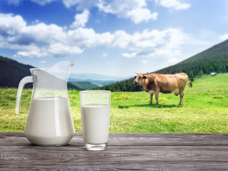 Fresh milk in decanter and jug in the background of landscape wi