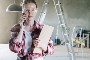 Young woman builder, architect, designer dressed in shirt and glasses is standing in workshop, talking on cell phone