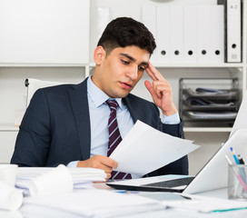 Young manager is reading documents about the transaction