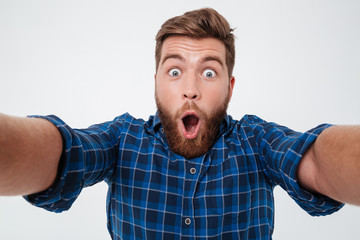 Close up picture of Shocked bearded man in checkered shirt