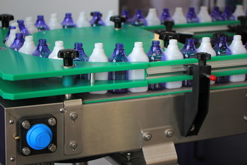Blue and while plastic liter bottles on the assembly line packaging machine pouring.