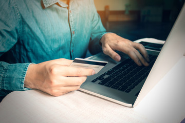 Man pressing keyboard and holding credit card with shopping online concept.