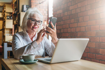 Businesswoman in glasses is sitting at table in front of laptop and using smartphone.Education for adults. Freelancer works.