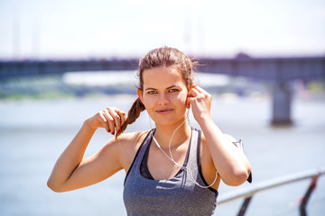 Sporty woman listening music before running. Female athlete listening music while doing sport.