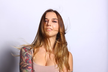 Beautiful woman face with natural skin. Perfect makeup. Wavy brunette hair. Beautiful tattoo on woman hand.