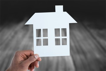 Composite image of hand holding a house in paper