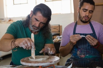 Male adult students making clay product