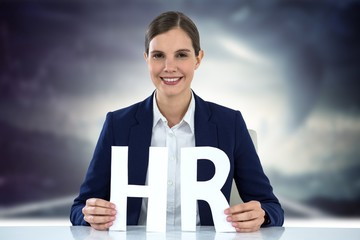 Composite image of business woman smiling and holding letters h