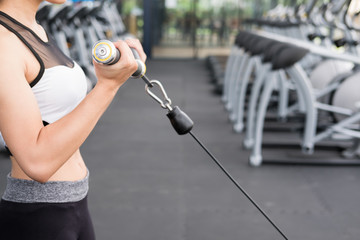 young woman execute exercise with machine in fitness center. female athlete pump up muscle with cable crossover in gym. sporty girl working out in health club.
