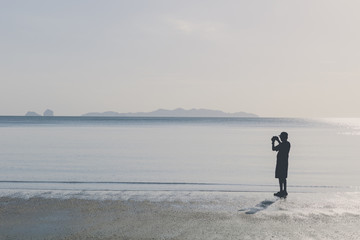 silhouette man take a photo on the beach nature landscape