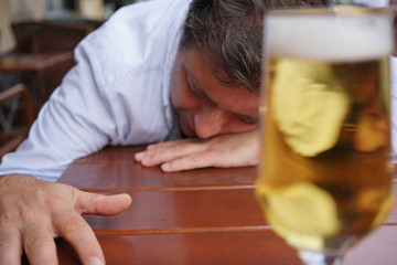 Young drunk man sleeping on the table in a bar