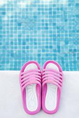 Pair of pink flip-flops on the swimming pool