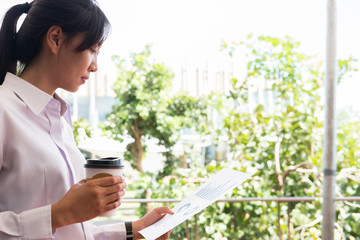 businesswoman holding coffee cup & financial summary graph outside office building. beautiful young asian woman with tea analyzing investment charts outdoors. business people with coffee woking online