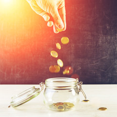 Front view of man hand putting coins into a glass jar on wooden table against dark background, toned image. Concept of investment, savings and business growth