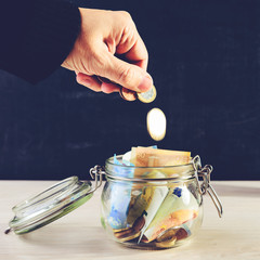 Front view of man hand putting coins into a glass jar with paper money on wooden table against dark background, toned image. Concept of investment, savings and business growth