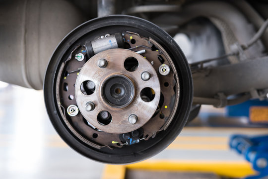 car suspension & bearing of wheel hub in auto service maintenance. Car lift up by hydraulic, waiting for tire replacement in garage. punched wheel concept