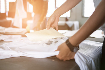 Young woman pull out paper from waterproof film on fabric at shop. worker working on manual screen printing on t-shirt. Wall mural