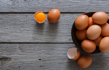 Brown and white organic eggs in bowl on wood background