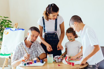 Family with two kids painting together at home, happy mother, father and children. Smiling family drawing together in kitchen at home. New housing, art and family leisure concept.