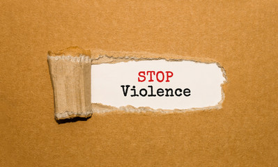 The text Stop Violence appearing behind torn brown paper