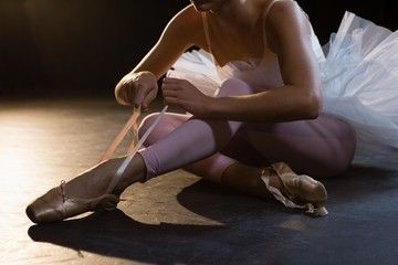 Ballerina tying her shoes