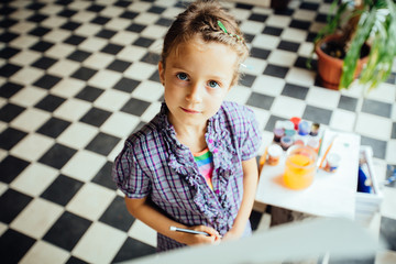 Top view of cute little girl with hair gathered in bunch before easel in studio or home over floor with checkerboard texture. Getting readu to school. Education, creation, art children concept.